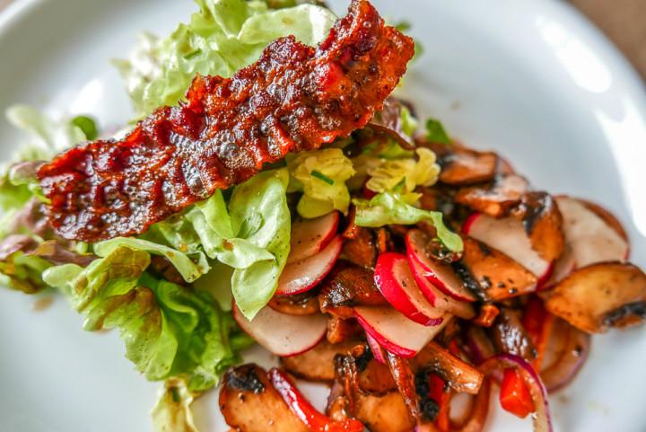 Herbst-Salat mit lauwarmen Pilzen, Radieschen, Paprika und kross gebratenem Schinken.