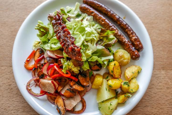 Der Herbstsalat eignet sich auch als Beilage zu einem herzhaften in der kühleren Jahreszeit. Hier mit Merguez und neuen Kartoffeln.