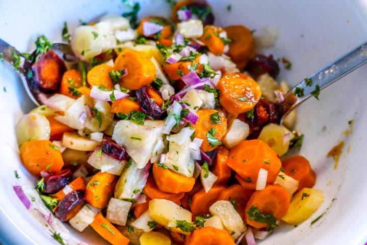 Das gekochte Karotten-Sellerie-Gemüse nimmt mehr Geschmack und Aroma auf, erst recht, wenn der Salat warm angemacht wird.